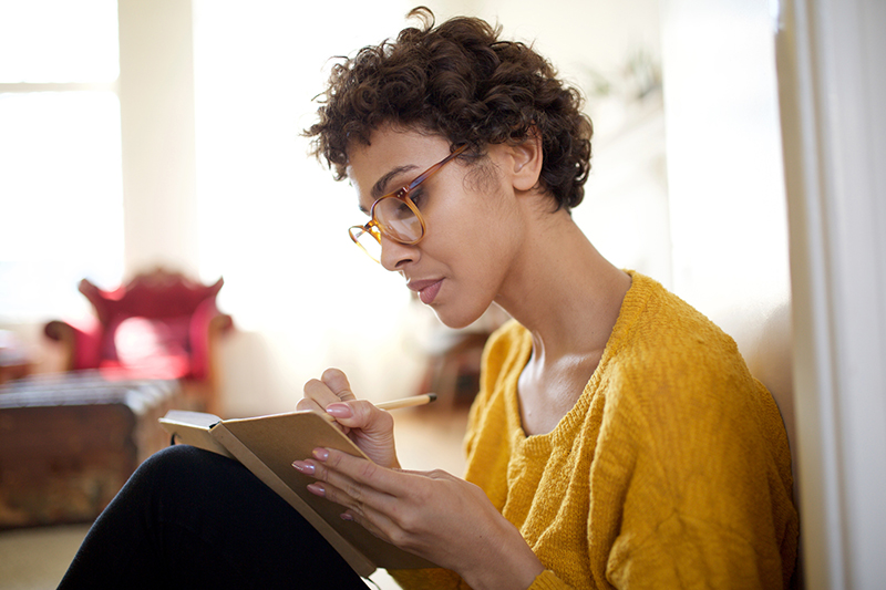 woman with glasses sitting and journaling