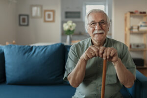 "Portrait of happy senior man smiling at home while holding walking cane. Old man relaxing on sofa and looking at camera. Portrait of elderly man enjoying retirement.""n"