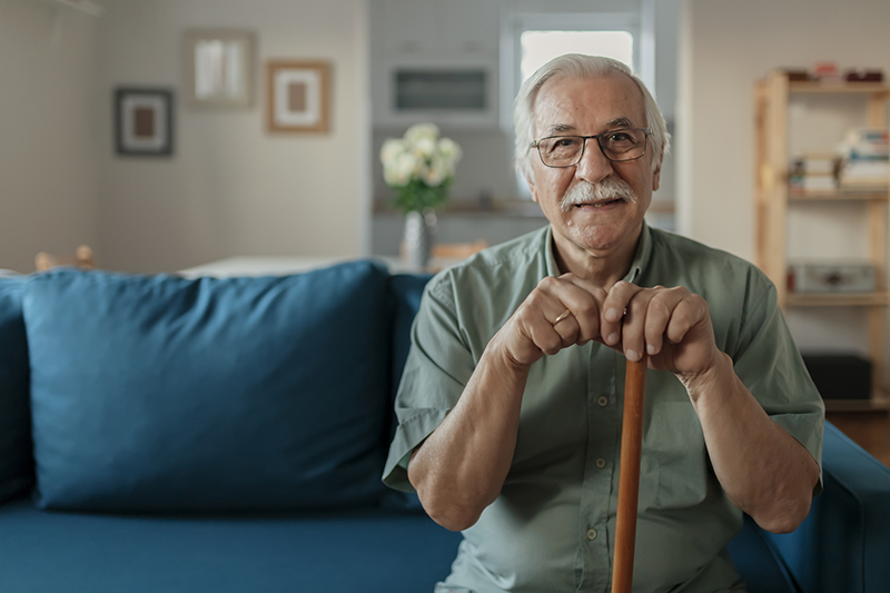 """Portrait of happy senior man smiling at home while holding walking cane. Old man relaxing on sofa and looking at camera. Portrait of elderly man enjoying retirement.""""n"""
