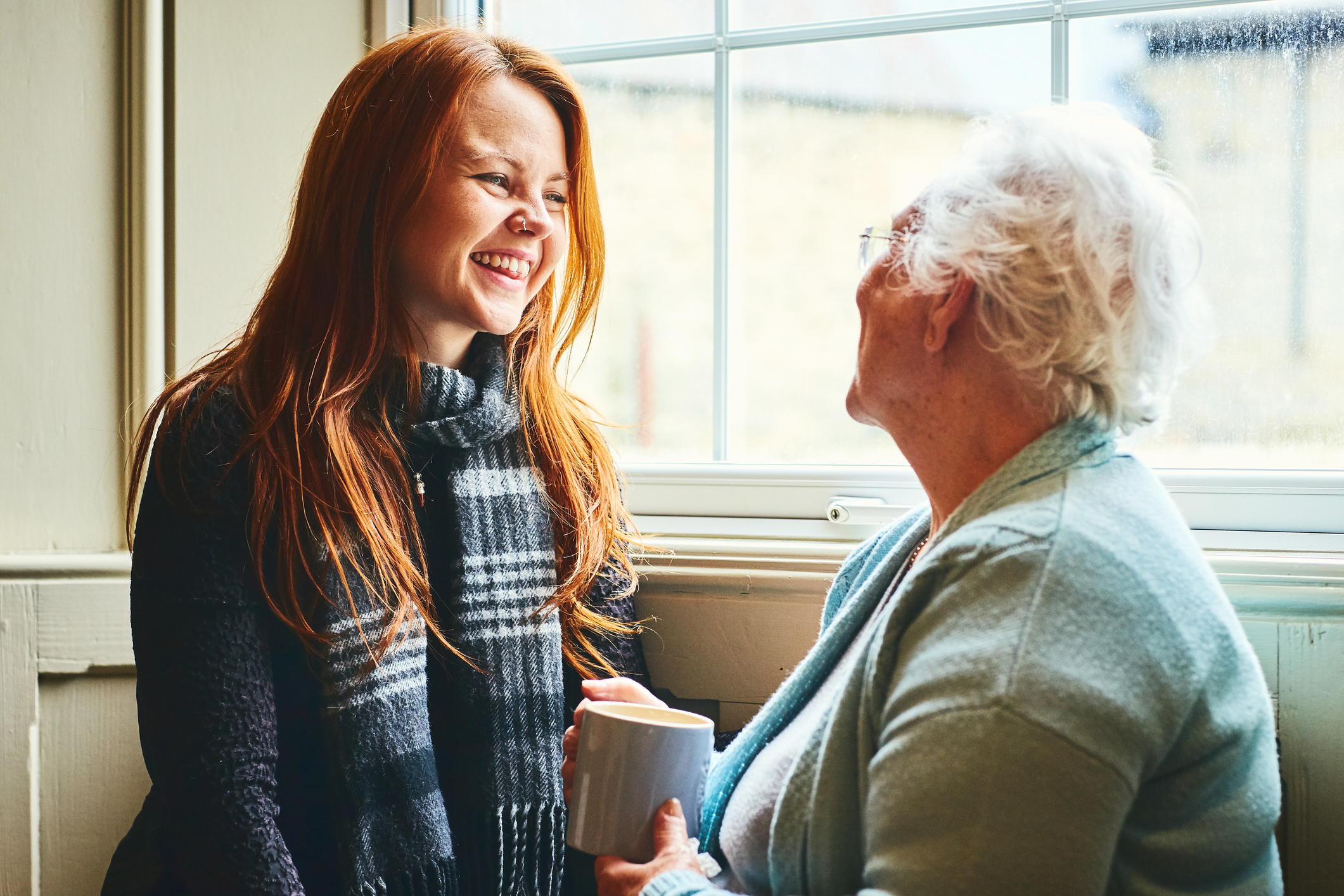 Young woman talking with senior woman about senior care solutions.